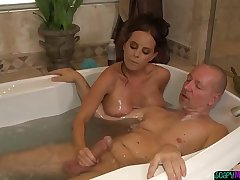 MILF masseuse tugging cock in the bathroom